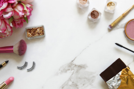 Beautifully styled bathroom counter with beauty products and pink flowers. White marble copy space.