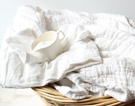 White linens in wicker basket with white powder laundry soap in cup. Reklamní fotografie