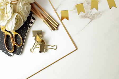 Elegant white, gold and black office supplies on white marble copy space.
