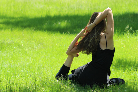 Young female seated in bright green grass stretching in yoga pose.