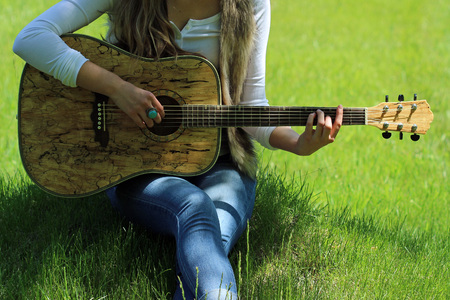 Young female dressed in bohemian fashion strumming guitar in  bright green grass.