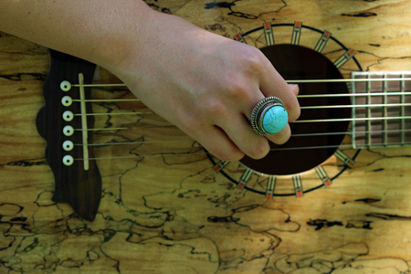 Close up of female hand strumming guitar with turquoise ring