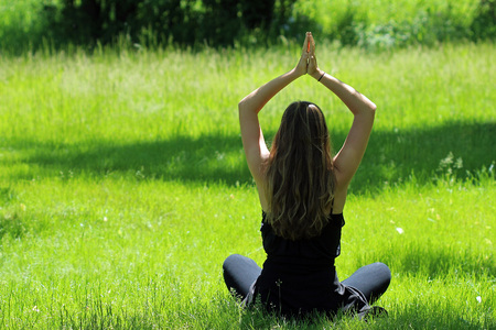 Young female seated in bright green grass doing yoga pose.