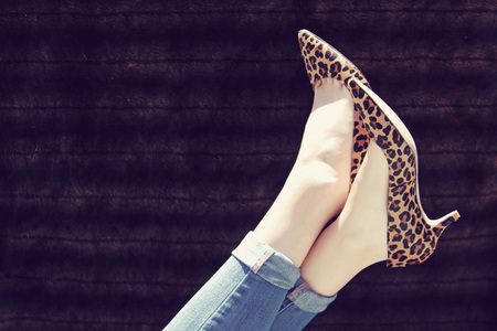 Feet with leopard print heels kicked up in the air