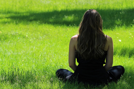 Young female seated doing yoga in bright green grass.