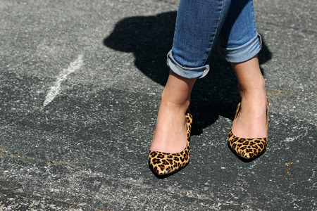 Leopard print heels and blue jeans walking on the city streets.