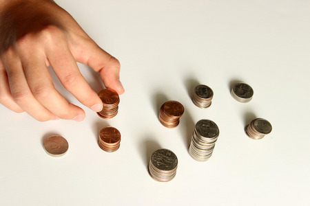 Female hand counting coins against white background. Stok Fotoğraf