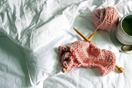 Above view of white bed with pink wool knitting project and a cup of tea.