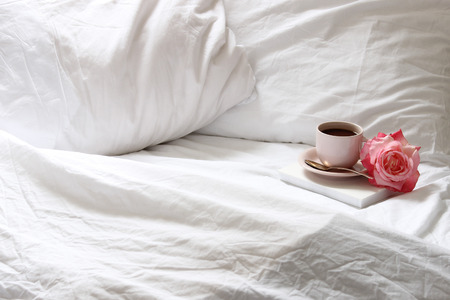 Open, unmade bed with coffee cup, book  and flower. Copy space Reklamní fotografie