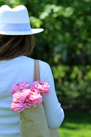 Young female dresses in summer fashion with hat and a bag of flowers in her bag
