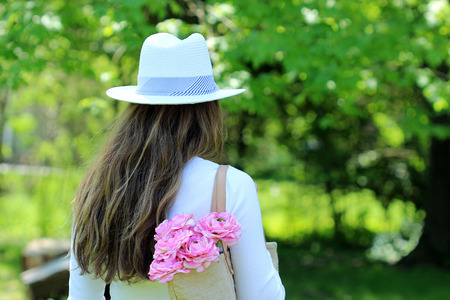 Young female dresses in summer fashion with hat and a bag of flowers in her bag.