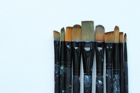 Paintbrushes in a row at varying sizes. White copy space.