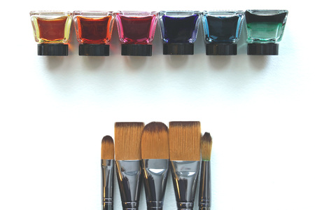 Rainbow colored liquid watercolors in a row with silver paintbrushes opposite. Copy space.