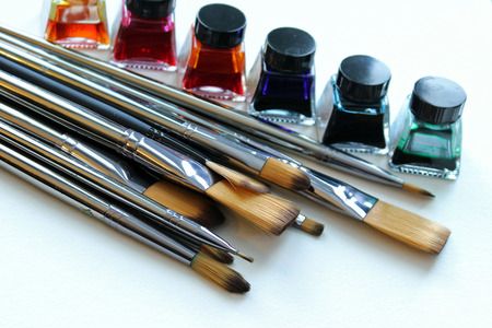 Large pile of silver metal paintbrushes with rainbow colored watercolor paints in background. Copy space.