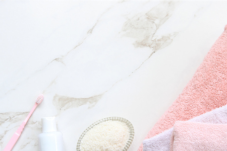Pink and white bathroom essentials on white marble copy space. Reklamní fotografie