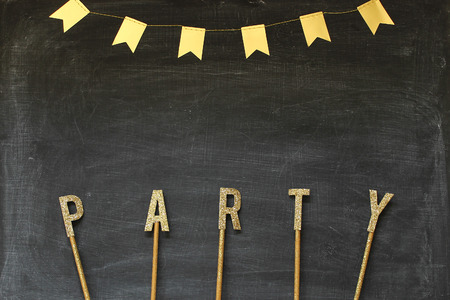 Party in gold letter with gold banner against open black board space for copy.