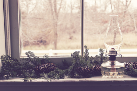 Naturally decorated window ledge with greens and oil lamp for Christmas.