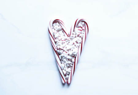 Crushed peppermint candy inside two candy canes shaped into a heart.
