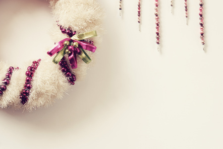 Vintage white wreath with pink and green ornaments.