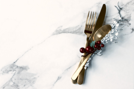 Gold cutlery with winter accents against white marble background.