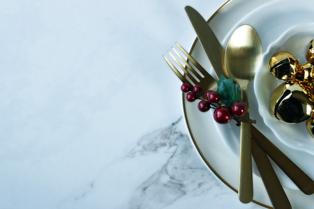 Modern styled table setting with gold accents and Christmas decor. Copy space. Reklamní fotografie