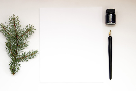 Nature styled desktop with pine branch, blank paper and pen and ink. Copy space.