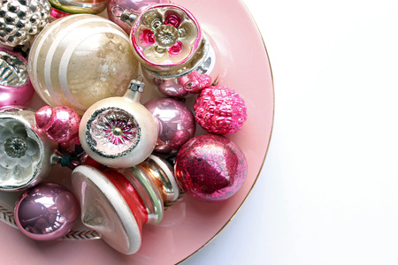 Pastel colored vintage ornaments on pink plate. White copy space.