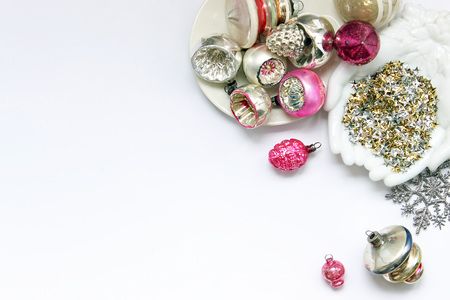 Pink and silver vintage ornaments on a white desk with stars, snowflake and open hands. Copy space.