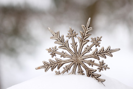 Silver snowflake in a pile of snow. Copy space. Reklamní fotografie