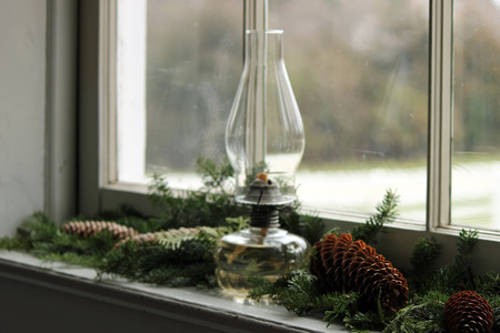 Vintage glass oil lamp on nature inspired Christmas decor in front of glass window.