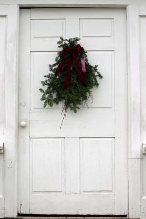 Pine bough with ribbon on white door.