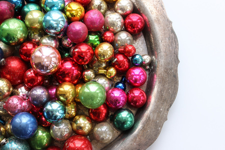 Multi-colored vintage ornaments on silver platter. Copy space.