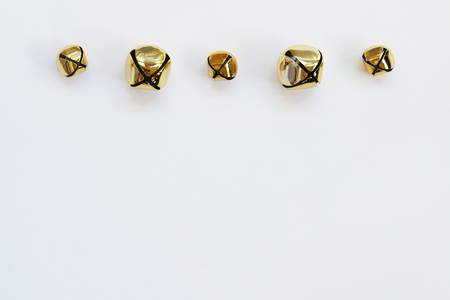 Five assorted jingle bells in a row against white background.
