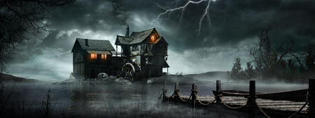 Night scene with old watermill, stormy sky and foggy lake