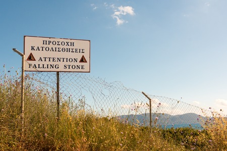 steep cliff sign: Warning sign at a dangerous cliff in Greece