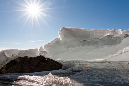 brightly: HDR photo of the melting ice at a Finnish lakeside with sun shining brightly in the background