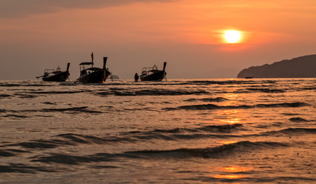 longtail: Three wooden long-tail boats floating at the sea during sunset in Krabi, Thailand
