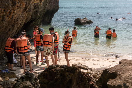 ding: KOH LAO LA DING, KRABI, THAILAND - JANUARY 25: Group of young tourists are preparing for snorkeling with safety life jackets on January 25, 2014 in Koh Lao La Ding, Krabi, Thailand