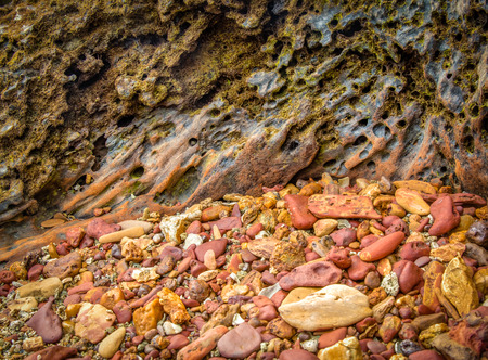 holed: HDR photo of the vibrant textures of red stones and old rugged wood covered by moss at a remote beach in Koh Lanta, Thailand Stock Photo
