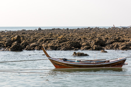 rowing boat: Small wooden Thai rowing boat floating at a shore in Koh Lanta, Thailand.