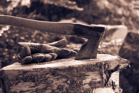 work gloves: Vintage style split-toned black and white photo of an old axe and work gloves on a firewood chopping block.
