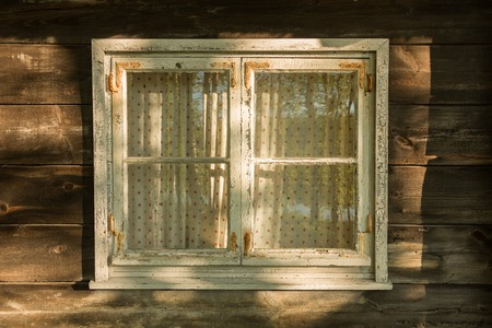 nostalgy: Window with a wooden frame of an old log house Stock Photo