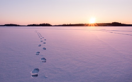 Footprints leading towards the sunset on the snow of a frozen lake. Stock Photo
