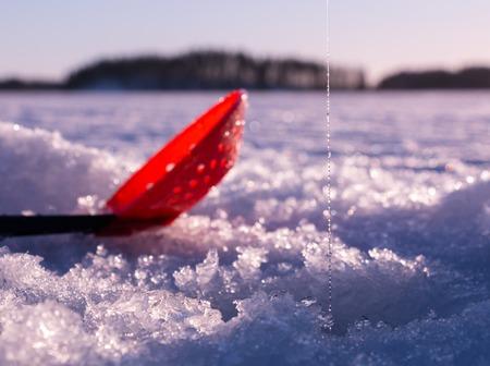 granizados: Plástico aguanieve skimmer cucharada se establecen sobre hielo por un agujero de la pesca de hielo con hilo de pescar.