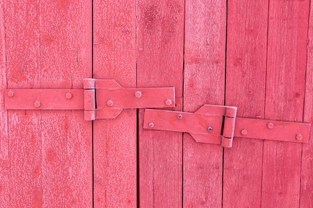 boathouse: Old door hinges of a wooden building painted red.