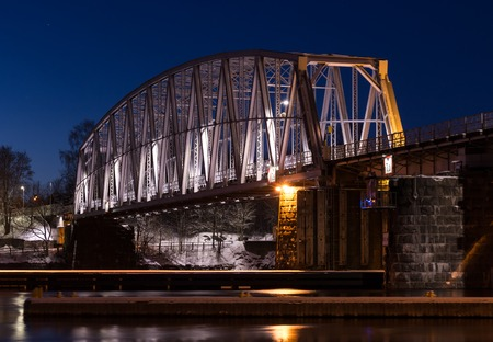 nightly: Nightly railroad bridge over streaming water with snowy surroundings.