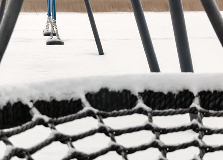 netting: Snowy spiderweb-styled circular rope netting of a swing at a playgrond in winter