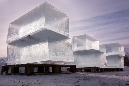 Huge blocks of clear ice severed for ice sculpture loaded on wooden pallets with beautiful backlight.