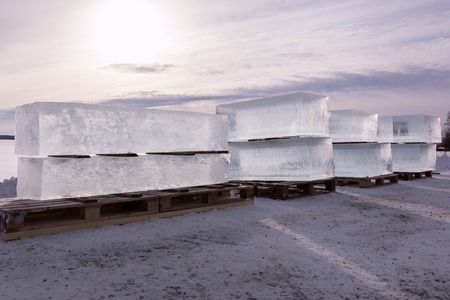 loaded: Backlight shot of a row of large ice cubes loaded for transportation on wooden pallets in Finland.