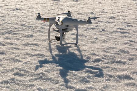 phantom: SAVONLINNA, FINLAND - MARCH 22: DJI Phantom 3 Professional quadcopter standing on snow cover before takeoff on March 22, 2016 in Savonlinna, Finland